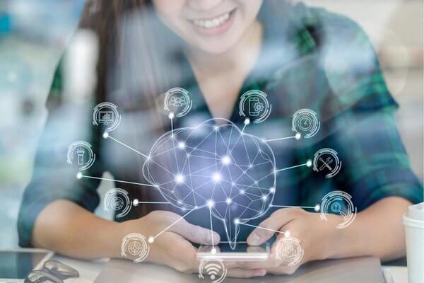 Mulher usando um celular, sobre o qual há vários ícones futuristas, com linhas e pontos conectados entre si na cor azul, simbolizando a modernidade e abrangência da internet das coisas.