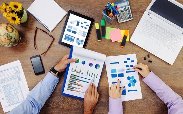 Mãos de duas pessoas segurando folhas com gráficos. Na mesa, também há um tablet com gráficos em sua tela, uma calculadora, um notebook, um celular, alguns post-its, um caderno e dois vasos de flores.
