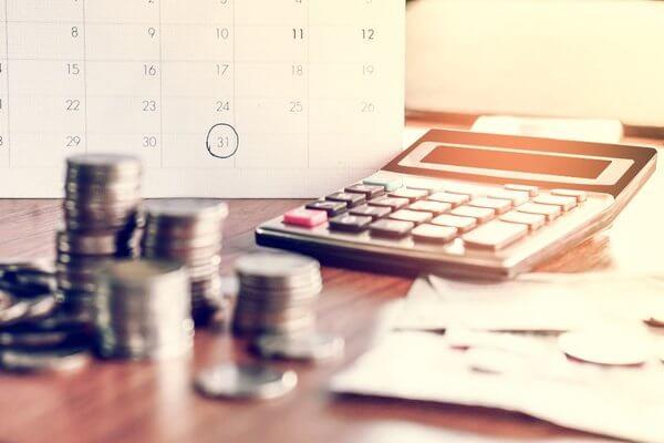 Close de uma mesa de trabalho, com algumas moedas, uma chave, uma calculadora e, ao fundo, um calendário com o dia 31 circulado, indicando o processo para manter as despesas controladas.