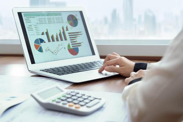 Executivo utilizando um notebook em uma mesa de escritório, com alguns papeis e uma calculadora. Na tela do notebook, aparecem gráficos e números, simbolizando o controle financeiro em empresas.