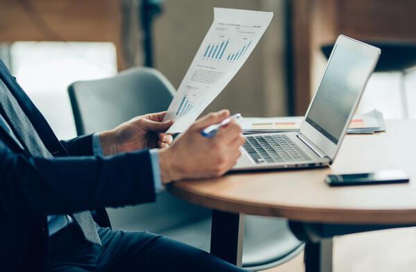 Executivo em uma mesa de trabalho, com um celular e um notebook, segurando uma caneta em uma mão e uma folha com gráficos na outra, simbolizando o controle dos principais gastos da empresa.