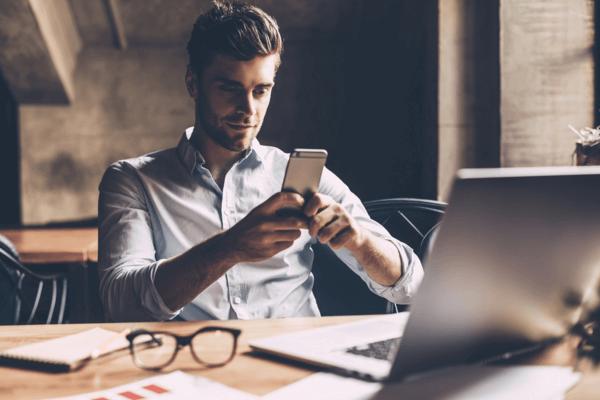 Profissional em uma mesa de trabalho, na qual ha um notebook, um óculos e alguns papeis. Ele está usando seu celular, indicando que os problemas de telefonia corporativa foram eliminados da empresa.